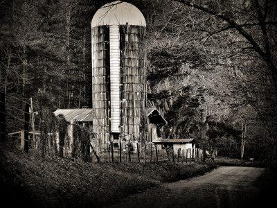 Black and white art featuring barn and grain silo