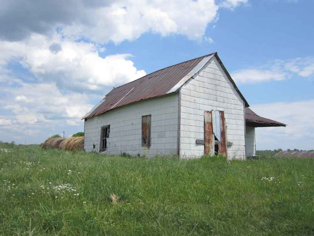 Original image of abandoned white building in green hayfield