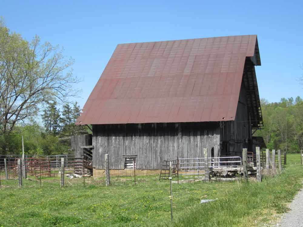 Original image of tall wooden barn with steep metal roof in a paddock