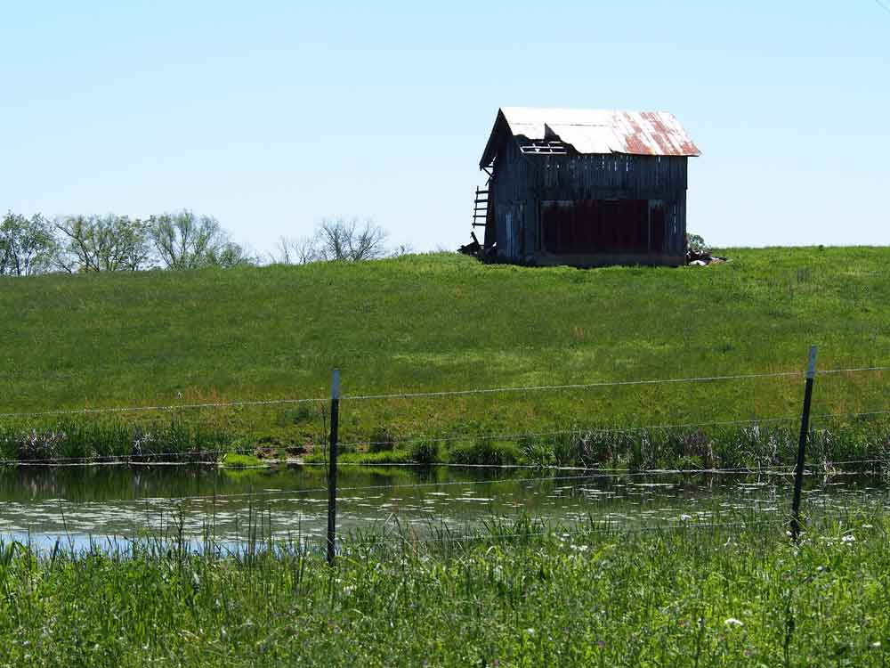 Original image of black barn with white metal roof on top of hill