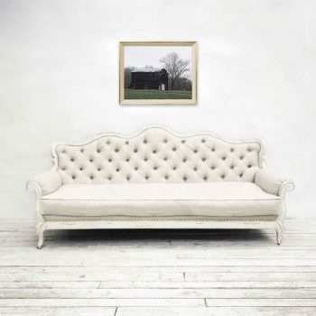 Photo of old black tobacco barn above white tufted couch
