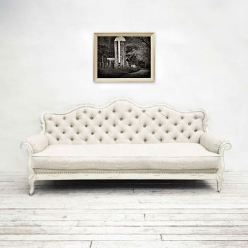 Black and white image of barn and grain silo hung over white living room couch
