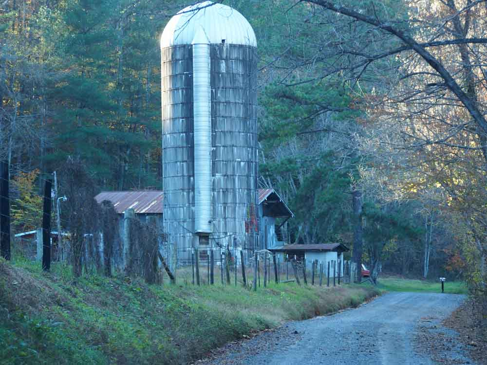 Original image of barn and large grain silo next to quiet country road