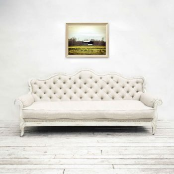 Rustic barn in field of yellow flowers on wall over white couch